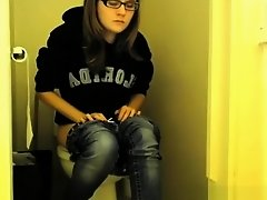 Girl in glasses pees in bathroom toilet on Watchteencam.com