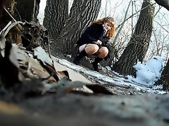 Ginger bridesmaid makes water behind a tree in the forest on Watchteencam.com